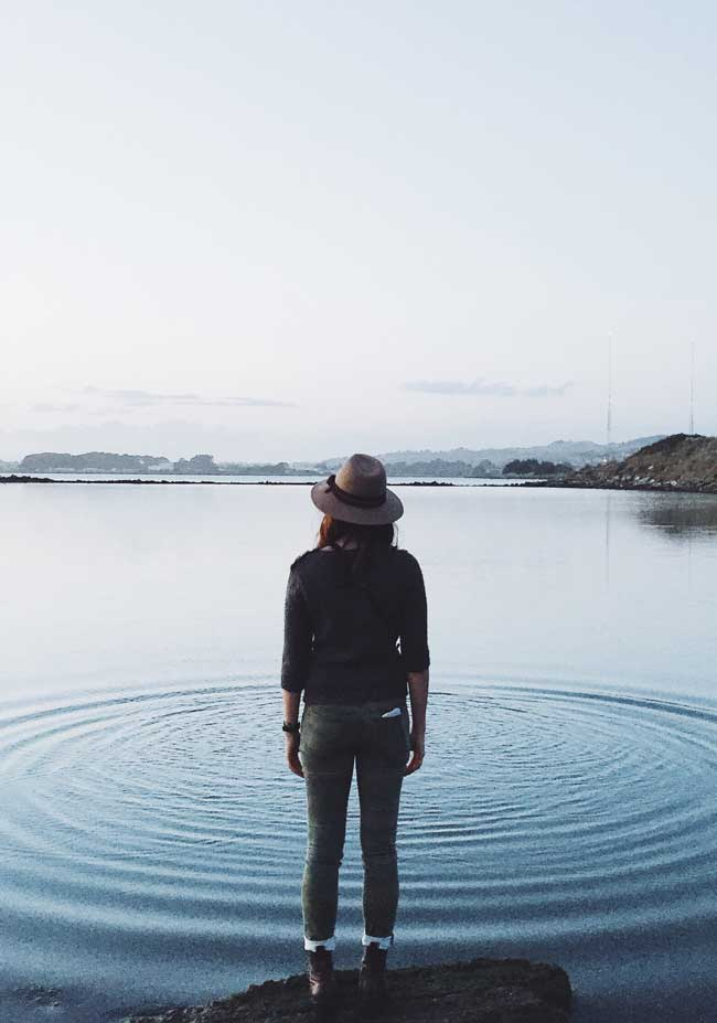 "woman standing in front of ripples on lake for ""Echoes of Mind, Resilience, and Action"""